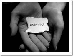 Hands holing a note with the word Happiness