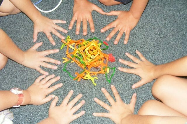 Children's hands around a plastic structure