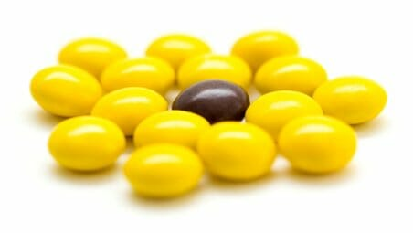 Brown skittle among yellow skittls