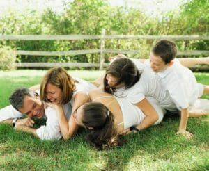 Parents and kids rolling on the grass laughing