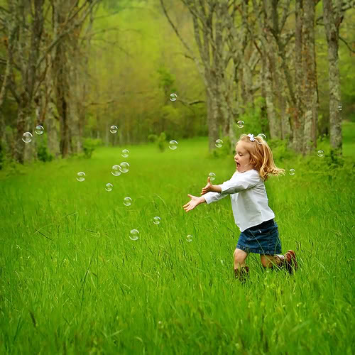 Happy girl chasing bubbles