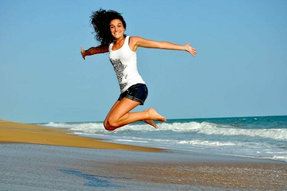 Happy woman jumping in the air on a beach