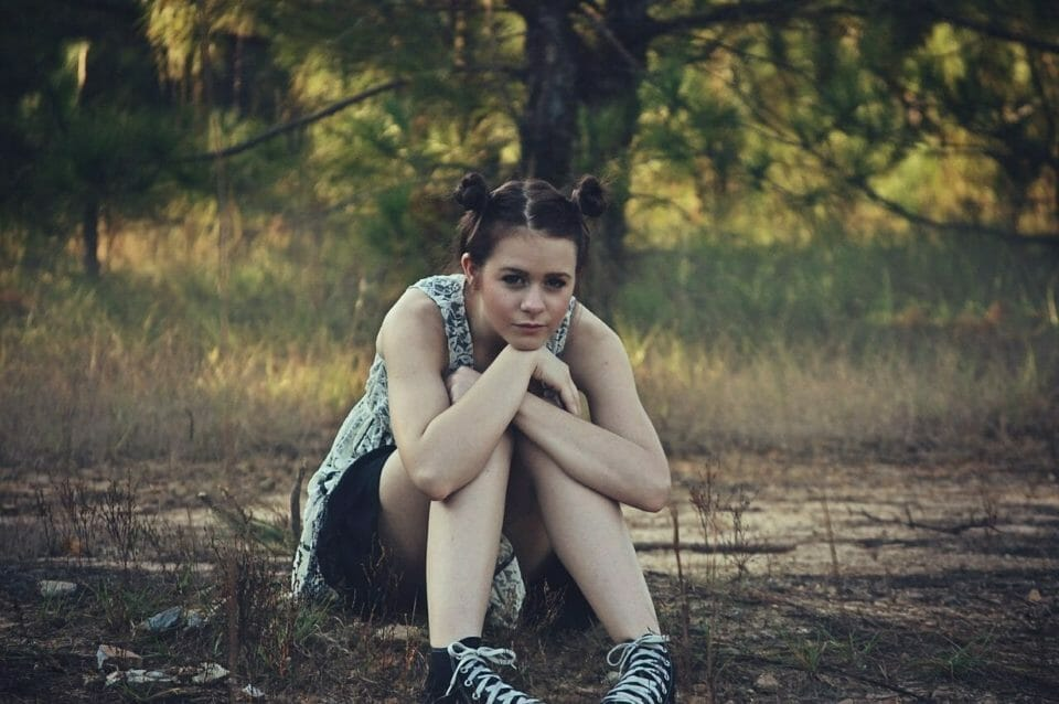 Teen girl sitting in a forest