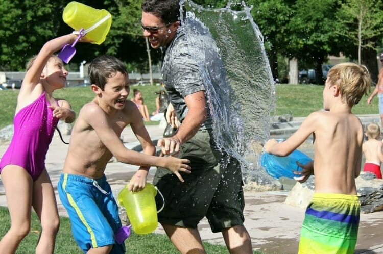 Kids having a water fight with a parent