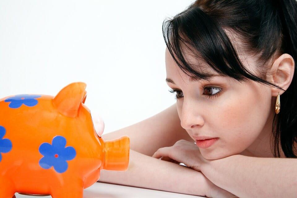 Woman staring at piggy bank