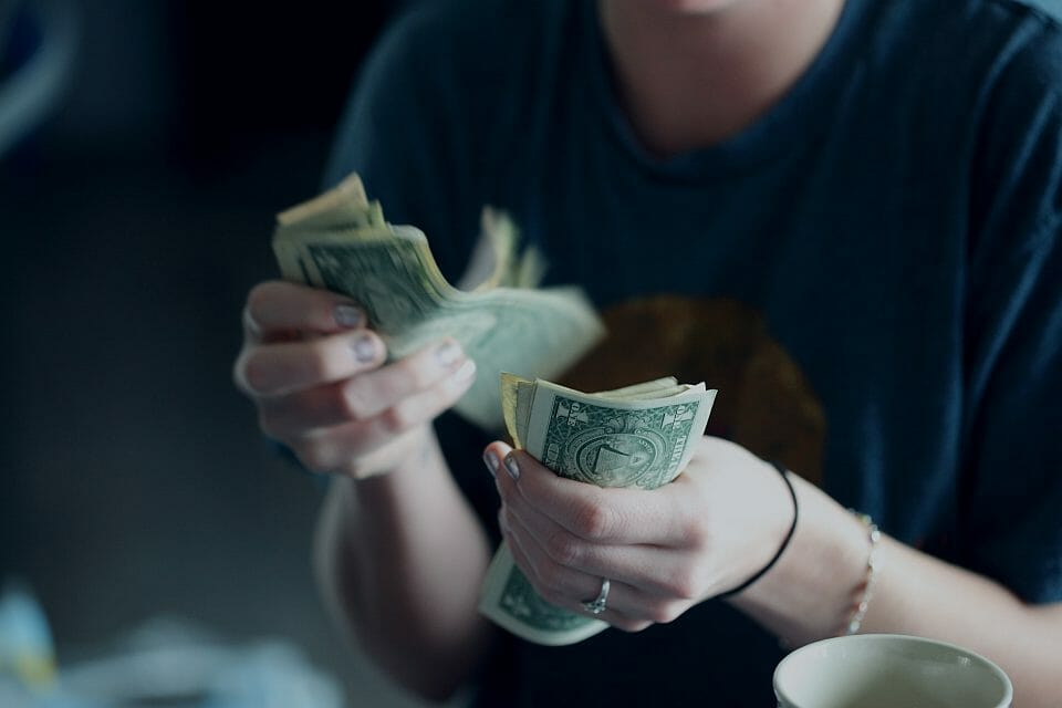 Young woman counting dollar notes