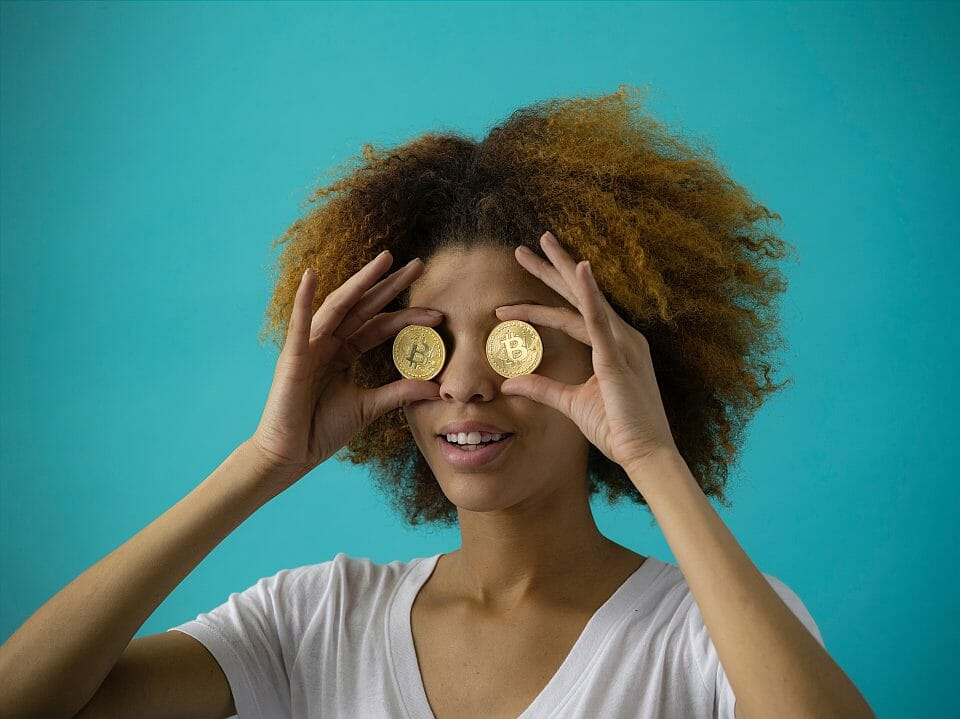 Young woman holding golden coins to her eyes